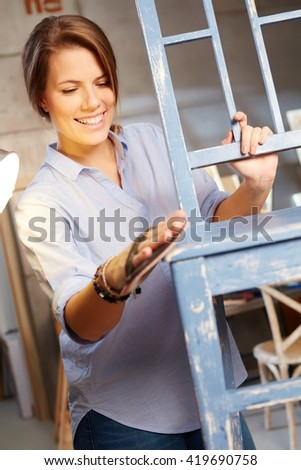 Happy woman renewing chair, polishing wooden surface. - stock photo