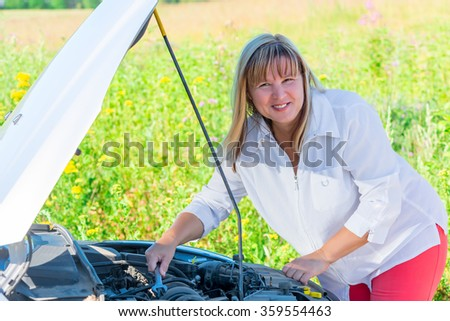 happy woman repairing the car on an empty road