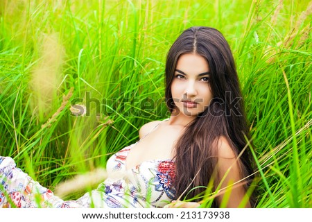 Happy woman resting and day lying down on green grass - stock photo