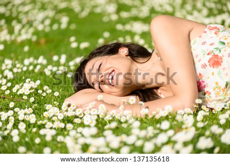 Happy woman resting and relaxing lying down on grass surrounded by flowers on park outdoors. Beautiful woman with closed eyes in spring dress napping and day dreaming. - stock photo