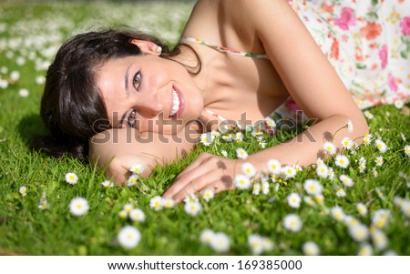 Happy woman resting and relaxing lying down on spring grass and flowers on park outdoors. - stock photo
