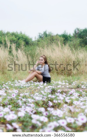 Happy woman resting and relaxing lying down on spring grass and flowers on park outdoors.