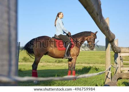 Happy woman riding horse outdoor while looking away and laughing.