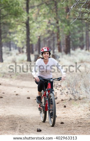 Happy woman riding mountain bike on wilderness trail
