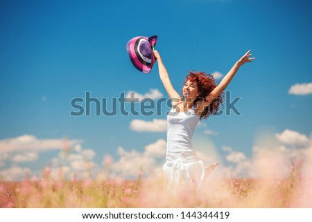 Happy woman running in the field with flowers at sunny day in the countryside. Free woman enjoying the nature. Beautiful girl outdoor. Freedom concept. Woman over sky and sun. Enjoyment and happiness