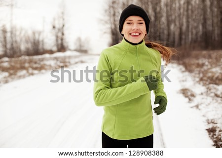 Happy woman running in winter - stock photo