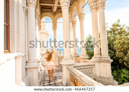Happy woman running on the castle terrace near the sea. General plan with columns and arches