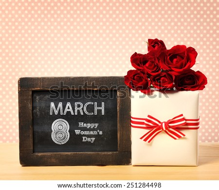 Happy Woman's Day message written on little chalkboard with roses and present box - stock photo