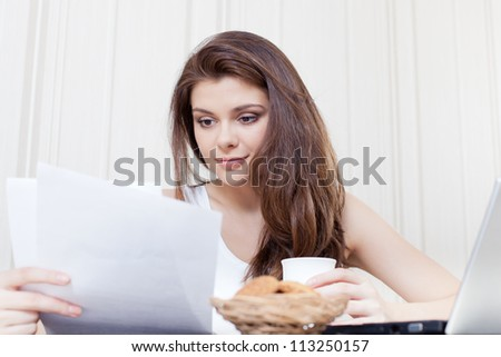 Happy woman seated at her desk and reading documents during a break
