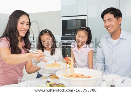 Happy woman serving food for the family in the kitchen at home