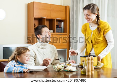 Happy woman serving soup her husband and child  in home