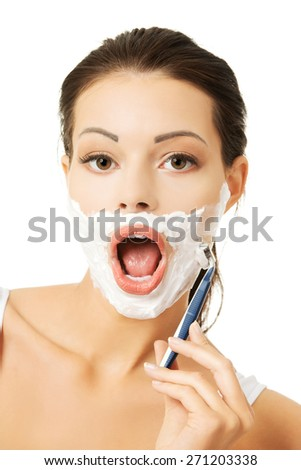 Happy woman shaving her face.