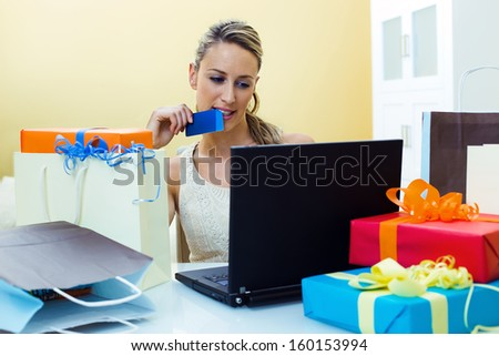 Happy woman shopping online at computer with credit card and the table full shopping bags - stock photo