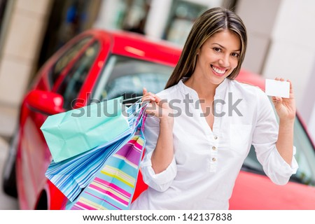 Happy woman shoppping with credit card to win a car - stock photo