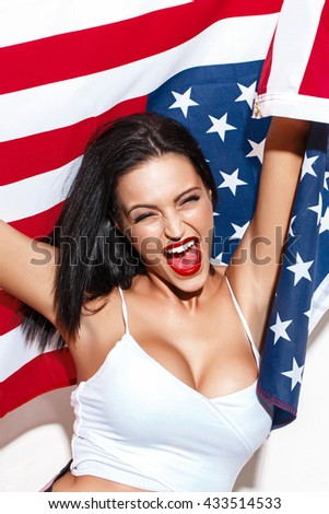 Happy woman shout with USA flag at white wall, open mouth, closed eyes