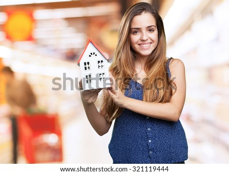 happy woman showing a house on white