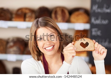 Happy woman showing bread with heart shape - stock photo