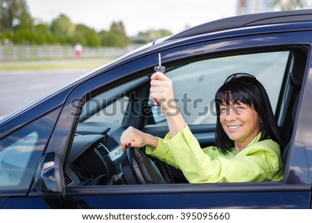Happy Woman Showing Car Key sitting in car with spring-summer mood. Dressed in green jacket with sun glasses on head. Woman Driving