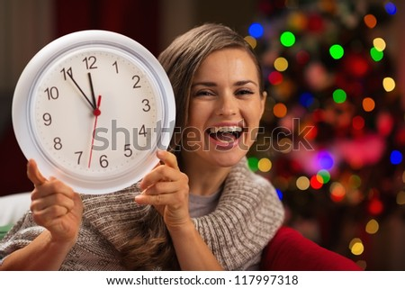 Happy woman showing clock in front of Christmas tree - stock photo