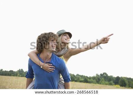 Happy woman showing something while enjoying piggyback ride on man in field - stock photo