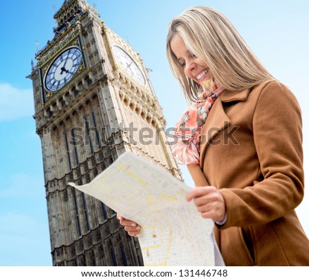 Happy woman sightseeing in London holding a map and smiling