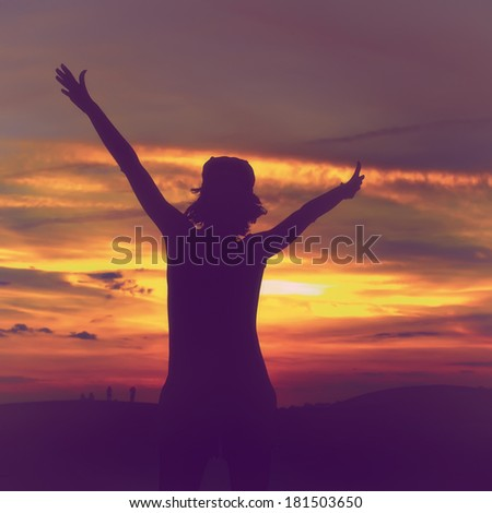 Happy woman silhouette standing against sunset with arms raised up - stock photo