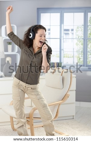 Happy woman singing and dancing with headphones at home, having fun. - stock photo