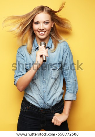 Happy woman singing in microphone over yellow background