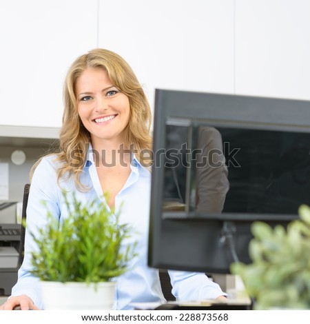 Happy woman sitting at her desk at work - stock photo