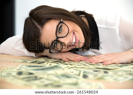 Happy woman sitting at the table with money - stock photo