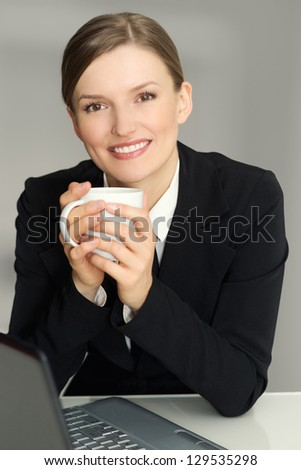 Happy woman sitting in armchair with laptop computer, holding coffee mug, looking at camera - stock photo