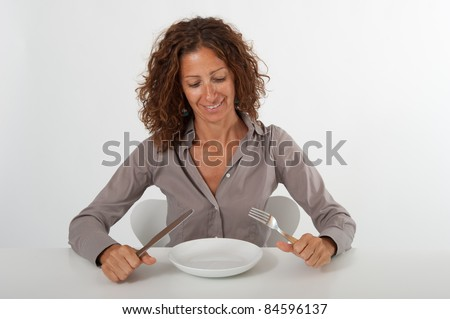 Happy woman sitting in front of an empty dish. Diet concept. You can place the food you prefer in the plate.