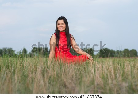 Happy woman sitting in the grass.