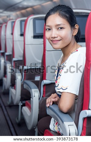 Happy woman sitting in the plane turns back. Passengers on the airplane is turning into an aisle. Asian tourists flying in an air plane. One happy traveler inside empty aircraft.