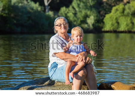 Happy Woman sitting near lake with granddaughter