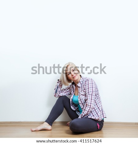 Happy woman sitting on floor with crossed legs in  casual clothing on white background in the studio