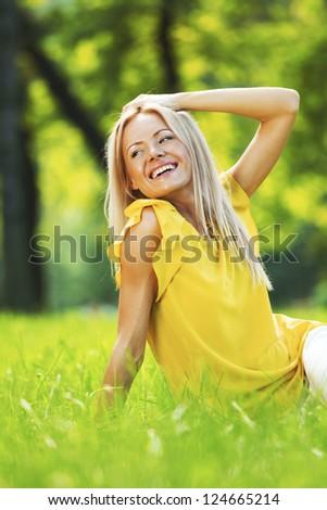 happy woman sitting on grass - stock photo