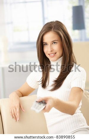 Happy woman sitting on sofa at home, using remote control, smiling.? - stock photo