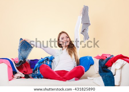 Happy woman sitting on sofa couch in messy living room holding clothes. Young girl surrounded by many stack of clothing. Disorder and mess at home. - stock photo