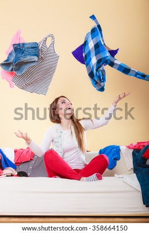 Happy woman sitting on sofa couch in messy living room throwing clothes. Young girl surrounded by many stack of clothing. Disorder and mess at home. - stock photo