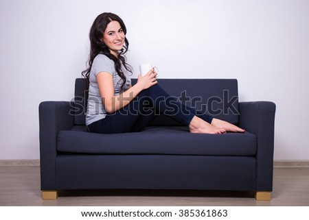 happy woman sitting on sofa with mug of tea or coffee
