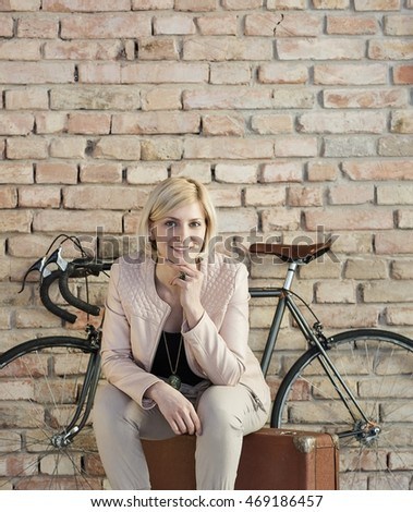Happy woman sitting on suitcase front of bicycle and brick wall.