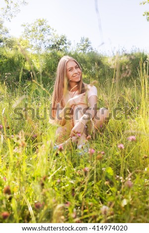 happy woman sitting on summer green grass