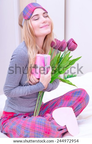 Happy woman sitting on the bed wearing cute pajama and with closed eyes with pleasure enjoying flowers and romantic gift in Valentine day - stock photo