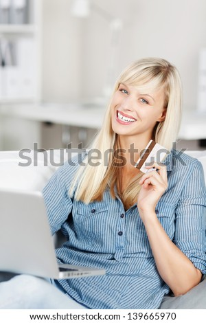 Happy woman sitting on the couch and holding a credit card and laptop