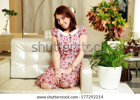 Happy woman sitting on the sofa at home - stock photo