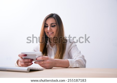 Happy woman sitting on the table and using smartphone