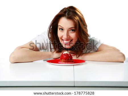 Happy woman sitting on the table with fresh strawberry cake isolated on a white background - stock photo