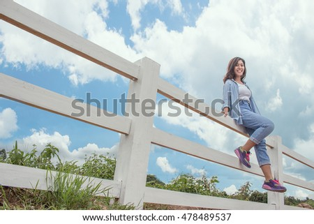 happy woman sitting on white fence and blue sky