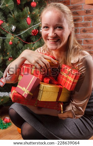 Happy woman sitting under Christmas tree with pile of Christmas presents - stock photo